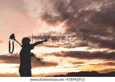 Silhouette of photographer pointing with beautiful sky in twilight time