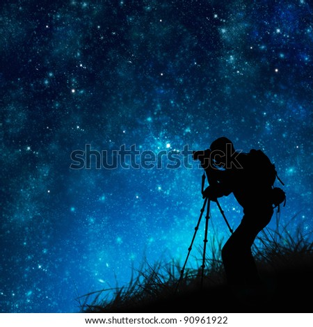 silhouette of photographer shooting stars - stock photo