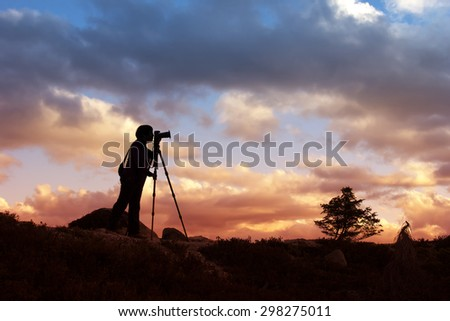 Silhouette of photographer taking photo in sunset - stock photo