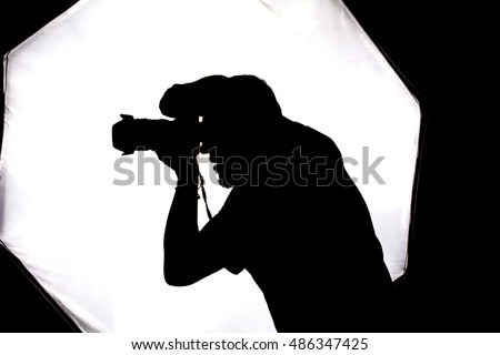 Silhouette of photographer taking pictures in studio with backlight