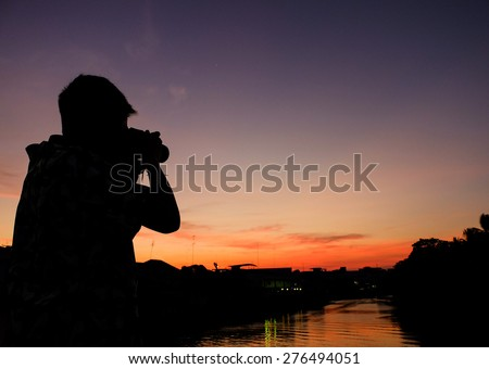 Silhouette of photographer with camera during sunset shooting a river photo