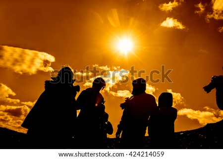 Silhouette of photographers standing on peak of mountain against sun with rays and blue sky with clouds.