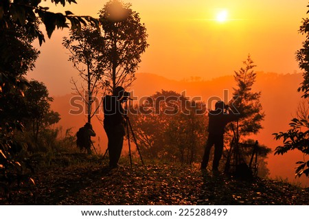 silhouette of photographers taking photos during sunrise