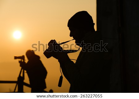 Silhouette of photographers taking photos of an amazing sun at the top of a hill. Amateur and professional working together.
