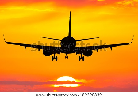 Silhouette of plane flying up at orange sunset  - stock photo