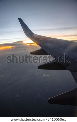 Silhouette of plane wing at sunrise
