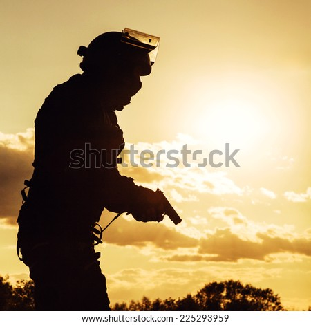 Silhouette of police officer with pistol at sunset - stock photo