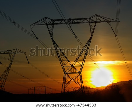 Silhouette of power lines at sunset - stock photo