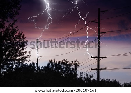 Silhouette of Power Lines being struck by lightning. - stock photo