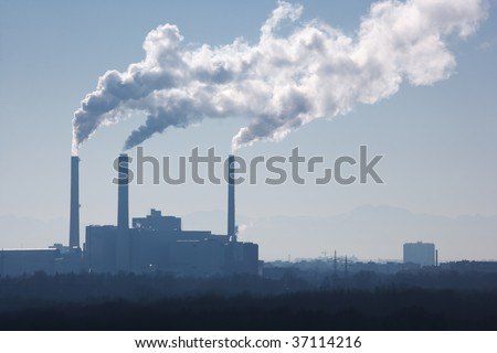 silhouette of power plant with smoke stacks - stock photo