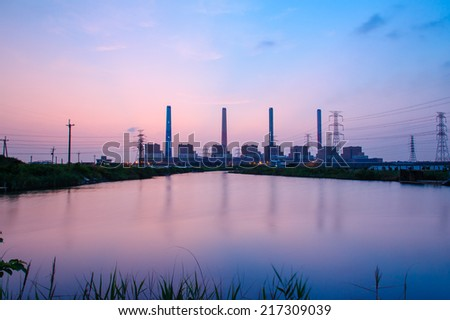 Silhouette of Power plant with sunset and reflection - stock photo