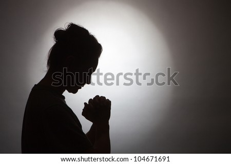Silhouette of praying woman - stock photo