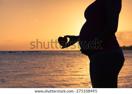 Silhouette of pregnant woman holding heart at sunset.  - stock photo