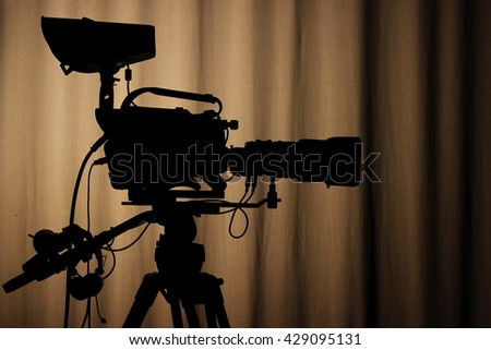 Silhouette of professional tv camera on a brown background - stock photo