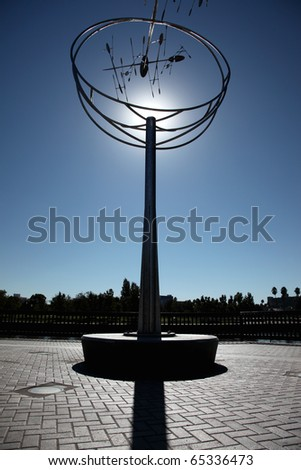 Silhouette of public park abstract modern art sculpture, sun directly behind. - stock photo