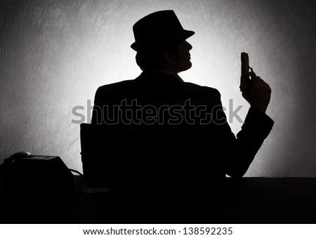 silhouette of retro style gangster holding his gun on grunge background - stock photo