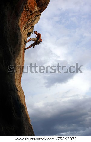 Silhouette of rock climber against cloudy sky background - stock photo