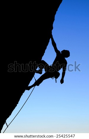 silhouette of rock climber climbing an overhanging cliff with blue sky background - stock photo