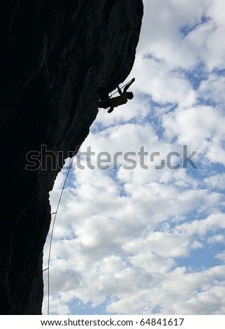 Silhouette of rock climber climbing an overhanging cliff with cloudy sky background - stock photo