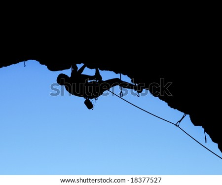 silhouette of rock climber climbing on a steep cliff