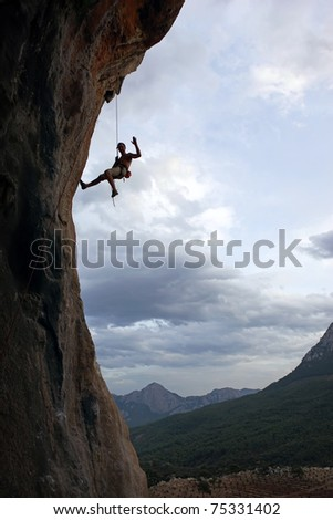 Silhouette of rock climber going down - stock photo