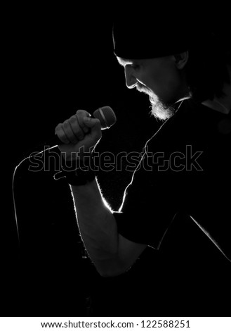 silhouette of rock singer with mike, all in black