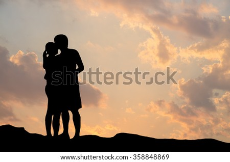 Silhouette of romantic a couple hug kissing against a summer twilight sunset sky