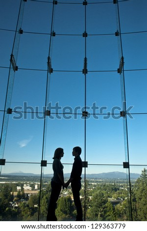 Silhouette of romantic couple in front of a big window - stock photo