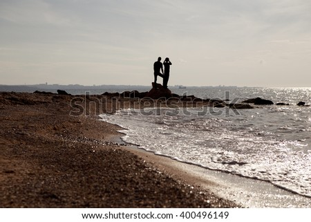 Silhouette of romantic couple on the beach travelers. - stock photo