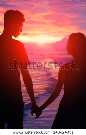 silhouette of romantic lovers hug with sea ocean and beautiful sunset - stock photo