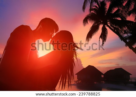 silhouette of romantic lovers hug with sea ocean in Maldives with sunset - stock photo