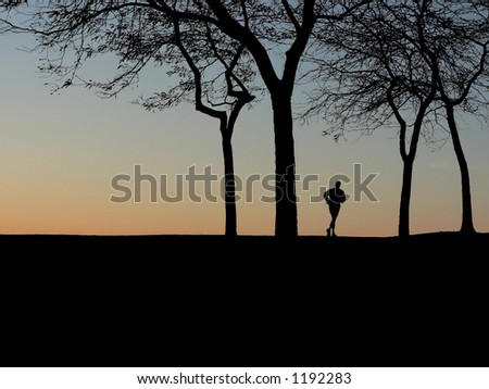 Silhouette of runner at dawn - stock photo
