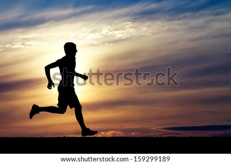 Silhouette of running man on sunset background