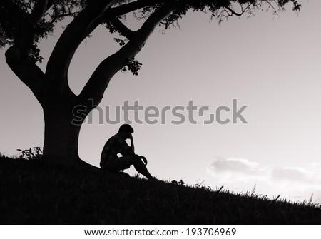 Silhouette of sad man sitting under the tree. - stock photo