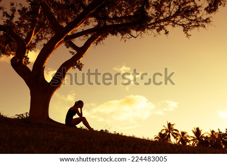 Silhouette of sad woman sitting under the tree - stock photo