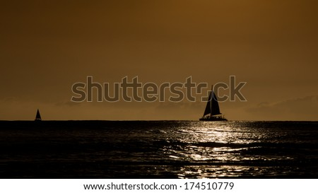 Silhouette of Sailboat at Sunset - stock photo