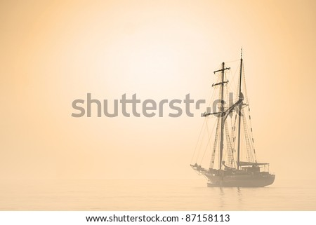 Silhouette of sailing ship in a misty morning lagoon. Backlit scene. Sepia toned. - stock photo