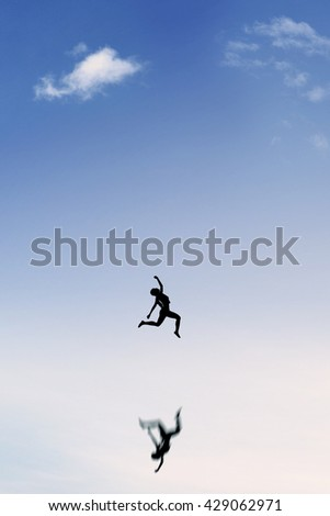 Silhouette of satisfied young woman leaps on the clear sky with reflection of her shadow