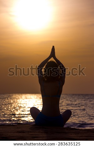 Silhouette of serene young woman practicing yoga, Sitting on the seashore at sunset or sunrise in asana Sukhasana, hands above head, back view - stock photo
