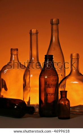 silhouette of seven ancient bottles over orange background - stock photo