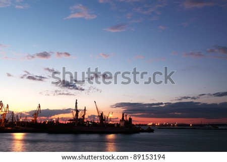 Silhouette of several cranes in a harbor, shot during sunset. Odessa, Ukraine - stock photo
