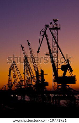 Silhouette of several cranes in a harbor,  sunset.