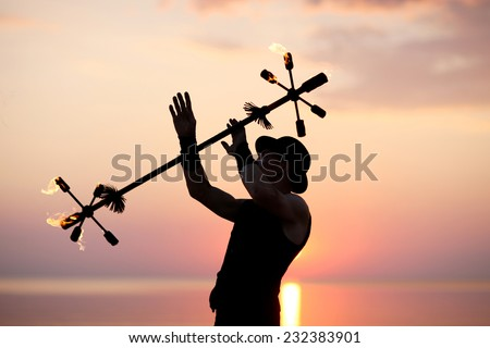 Silhouette of showman juggling with fire baton - stock photo