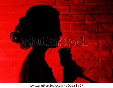 Silhouette of singing woman  on brick wall background - stock photo