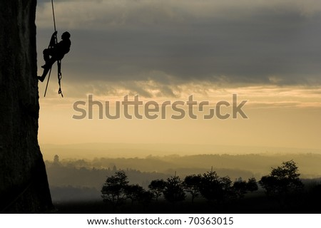 Silhouette of single rock climber against stunning sunset concept of achievement