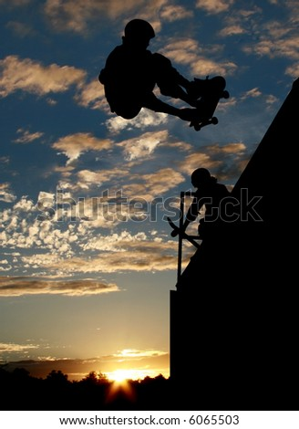 Silhouette of skateboarders on ramp at sunset - stock photo