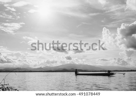 silhouette of small fishing boat in the lake with mountain view against cloudy sky at sunset in white tone