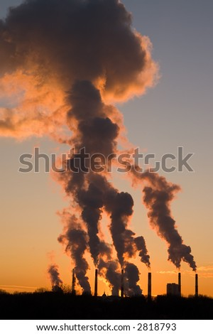 Silhouette of smoke stacks smoking into the sky at sunset