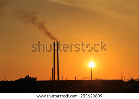 Silhouette of Smokestacks at sunset time - stock photo
