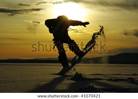 Silhouette of snowboarder jumps in powder - stock photo